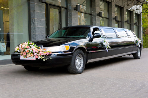 A black stretched limo with flowers.