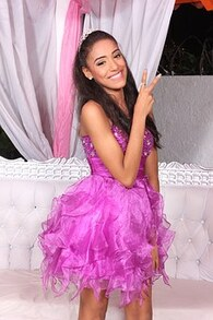 A birthday teenager striking a pose and smiling with the peace sign in her pink dress.