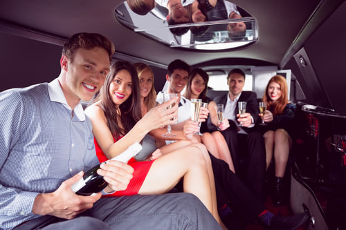 A group of friends enjoying champagne inside a limo.